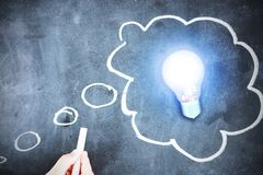 New brilliant idea is generated, with light bulb and chalk sketch on blackboard Royalty Free Stock Photo