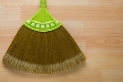 New broom made of synthetic Nylon fiber with green handle on woo Stock Images