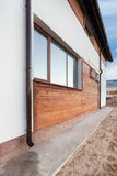 New brown copper gutter in house with white wall and wooden planks. Stock Photo