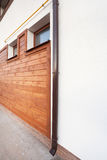 New brown copper gutter in house with white wall and wooden planks. Royalty Free Stock Photo