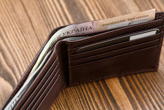 New brown leather wallet over dark wooden background. Stock Photos