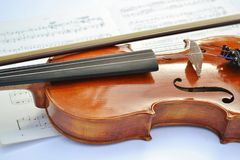 New brown wooden violin with a bow put along the music instrument and a sheet music under it. royalty free stock images