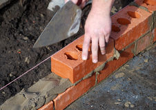 New build. Close-up of builder laying bricks of new build royalty free stock image