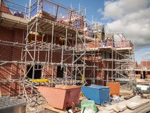 New build homes in scaffolding on an housing estate in Cheshire UK. New build houses under construction and in scaffolding near completion in Cheshire England royalty free stock images