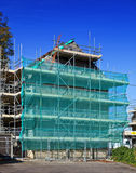 New Build House. With scaffolding and blue sky Stock Image