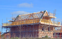 New build house with roof rafters and scaffolding. A new build house under construction showing wooden roof beams and scaffolding royalty free stock photography
