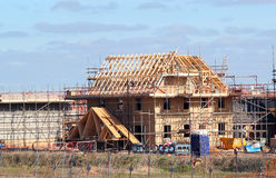 New build house with roof rafters and scaffolding. New build house under construction showing wooden roof beams and scaffolding. Building site stock image