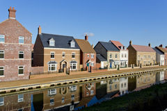 New build houses by a canal. In Swindon, Wiltshire, UK. Rather than having houses built in the same style, modern luxury estates utilise a mix of styles and Royalty Free Stock Photos