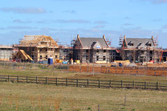New build houses with roof rafters and scaffolding. New build houseS under construction showing wooden roof beams and scaffolding Stock Image