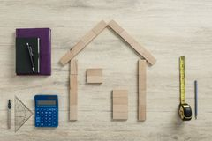 New build planning and costing concept. New build of a dream home planning and costing concept with a wood block outline of a house surrounded by calculator Stock Image