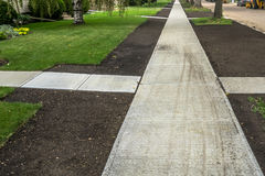 New Build Sidewalk. Sidewalk concrete work completed and the site has been prepared for sodding Stock Photo