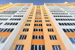 New building apartments painted orange on clear blue sky Royalty Free Stock Image
