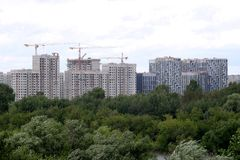New building construction in new district after river over sky with white clouds in summer day stock photo