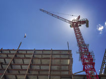 New building construction site. With giant crane aligning steel beams Stock Photo