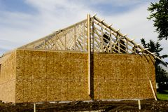 New building construction. New wooden building construction with a blue summer sky in the background stock images