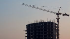 New building,new construction.Unfinished building.Construction crane with unfinished building on sky background.Crane and building royalty free stock photography