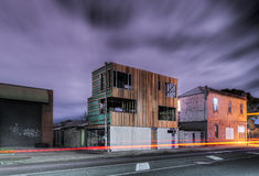 New Building, Old Building. Long exposure shot of suburban street corner at night with new building under construction next to old corner shop building Royalty Free Stock Photos