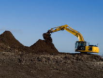 A new building project. A yellow backhoe busy with sand digging on a constructionsite as preparation for the building of new houses Royalty Free Stock Images