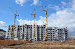 New building under construction with cranes against a blue cloudy sky. Building and cranes under construction against blue sky Royalty Free Stock Image