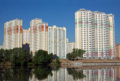 New buildings over river and clear blue sky in summer day Royalty Free Stock Photo