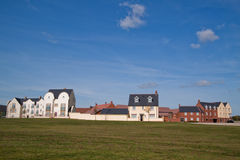 New Built Houses. Recently built houses with varying styles overlooking a green field Stock Photos