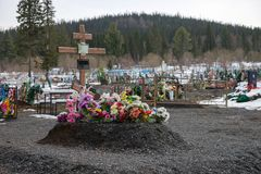 New burial with artificial flowers, on an old village cemetery. Siberia. Belogorsk. The Kemerovo Region. Russia. New burial with artificial flowers, on an old Stock Photography