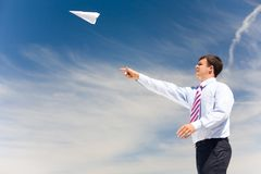 New business. Image of businessman letting paper airplane fly and looking at it on background of blue sky Royalty Free Stock Image