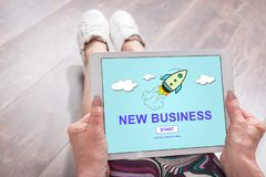 New business concept on a tablet. Woman sitting on the floor with a tablet showing new business concept stock image