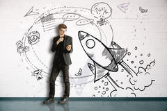 New business concept. Thoughtful businessman using smartphone in brick room with space ship sketch. New business concept. 3D Rendering Stock Image