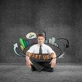 New business concept. Young businessman in concrete room sitting on floor with laptop and abstract startup sketch. New business concept Royalty Free Stock Photography