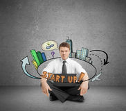 New business concept. Young businessperson in concrete room sitting on floor with laptop and abstract startup sketch. New business concept Stock Images