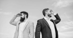 New business directions. Developing business direction. Businessmen bearded faces stand back to back sky background. Men stock images