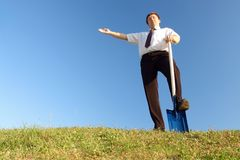 New business vision. Businessman in white shirt and tie standing on grass field with one foot resting on shovel showing with his right hand over clear blue sky stock images