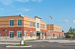 New Canadian Elementary School Building. A new Canadian elementary school building with flagpole and parking lot Stock Images