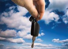 New car. Fingers holding car keys against a cloudy blue sky Stock Photography
