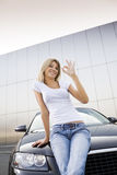 New car. Young woman leaning on new car and similing Stock Photos