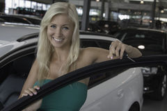 New car. Blond young woman holding the keys in a car dealership Royalty Free Stock Photo