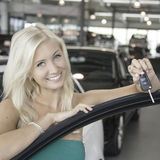 New car. Blond young woman holding the keys in a car dealershiop Royalty Free Stock Images