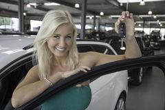 New car. Blond young woman holding the keys in a car dealershiop Royalty Free Stock Photo