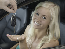 New car. Blond young woman receives the keys whilst sitting in the driver's seat of a car Royalty Free Stock Photos