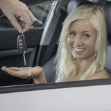 New car. Blond young woman receives the keys whilst sitting in the driver's seat of a car Stock Photo