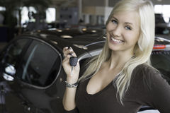 New car. Blond young woman standing with car keys in front   a new car in a car dealership Stock Image