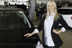 New car. Blond young woman standing next to a new car in a car dealership Royalty Free Stock Photos