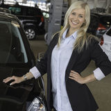 New car. Blond young woman standing next to a new car in a car dealership Royalty Free Stock Image
