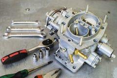New car carburetor at shallow depth of field. New car carburetor and tools with shallow depth of field Stock Photos