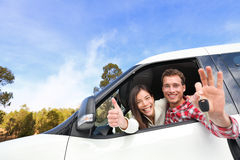 New car - happy couple showing car keys. Driving having fun on road trip drive in rental car. Happy lifestyle with beautiful young interracial couple outdoors Royalty Free Stock Photo