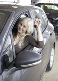 New car. Happy female sitting in brand new car flashing key Royalty Free Stock Photos