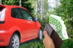 New car owner concept. Buying new sport car concept. Hand with money and car on the image royalty free stock image