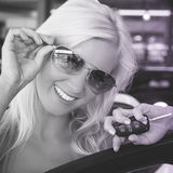 New car. Young blond smiling female holding car key in auto dealership Royalty Free Stock Photography