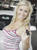 New car. Young blond smiling female holding car key in front of a new car stock image